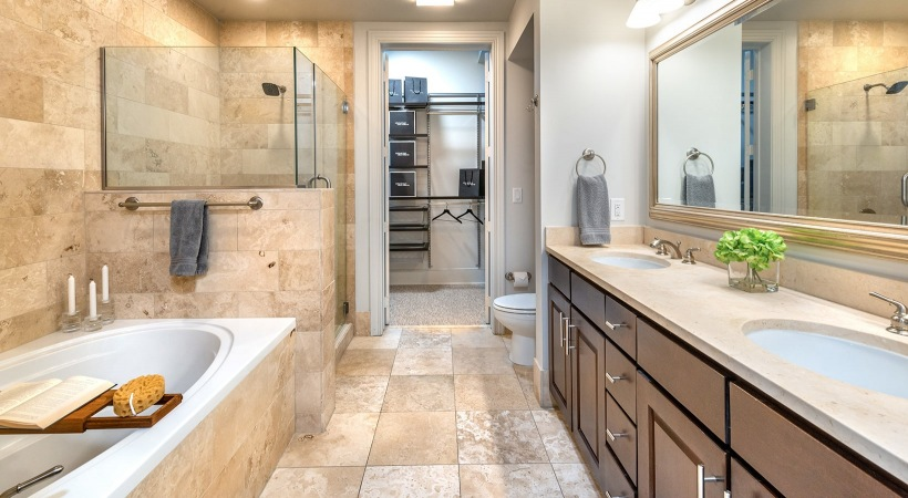 spacious bathroom with a large mirror, custom scone lighting and easy access to walk-in shower